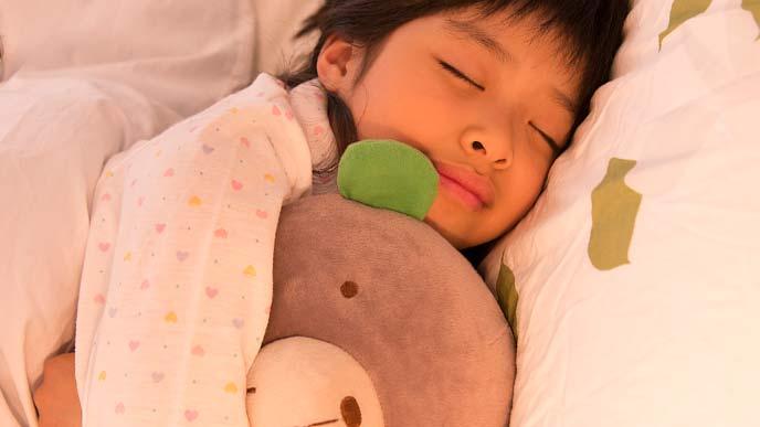 ぬいぐるみを抱いて眠る幼児