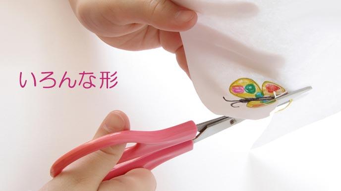 紙に描いた蝶々を挟みで切り取る