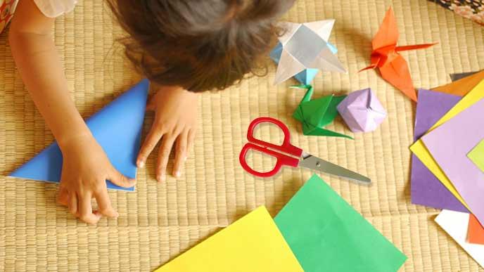 折り紙する子供の傍に置かれたハサミ
