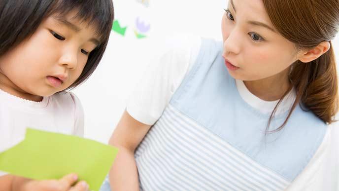 折り紙を持つ子供と見守る保育士