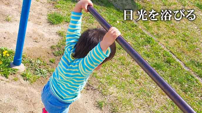 外で鉄棒にぶら下がる子供