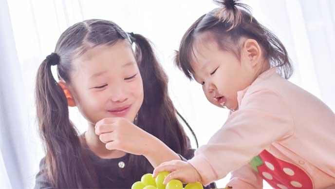 ぶどうを食べてる笑顔の姉妹