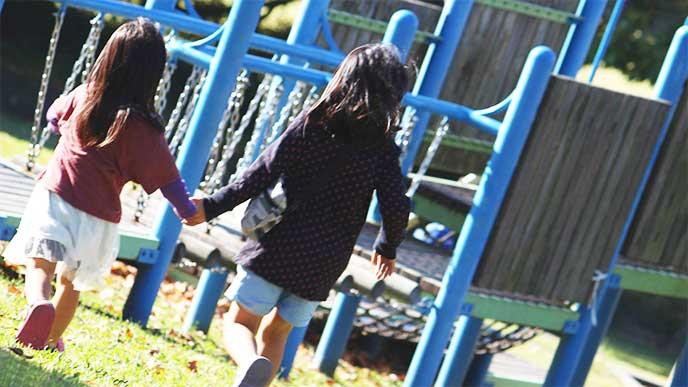お姉ちゃんに手を引かれて公園を走ってる女の子