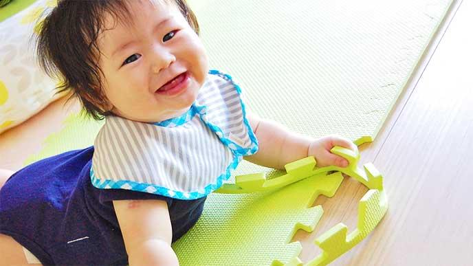 コルクマットの上で遊んでる赤ちゃん