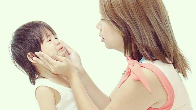 泣いてる子供の顔を見ながら優しく話しかける母親