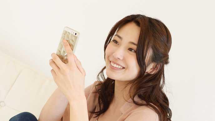 スマホでフリマアプリを操作してる女性
