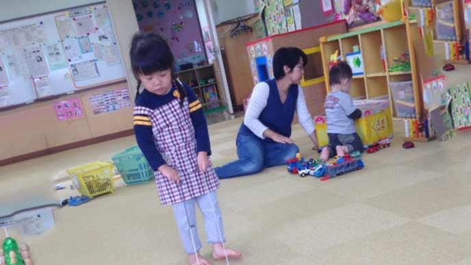 保育園で保育士と園児が玩具を探す