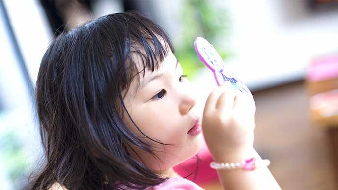鏡で自分の目元を見てる女の子