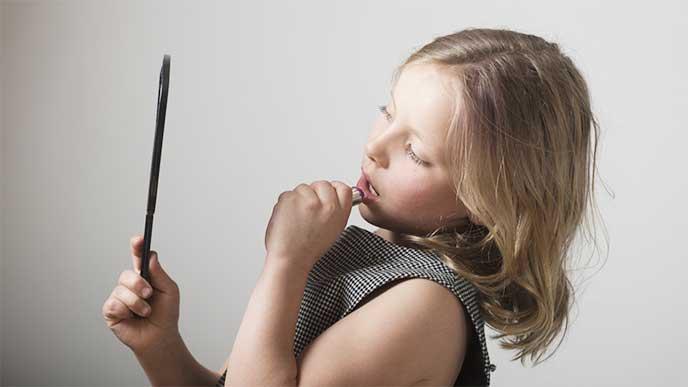 鏡を見ながら口紅を塗る大人っぽく見える小学生の女の子