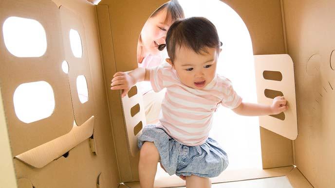 ダンボールハウスで遊ぶ幼児