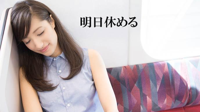 電車のシートで目を閉じる女性