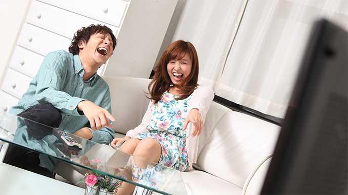 一緒にテレビを見て笑ってる夫婦