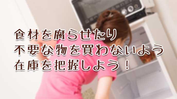 冷蔵庫の中をチェックする母親