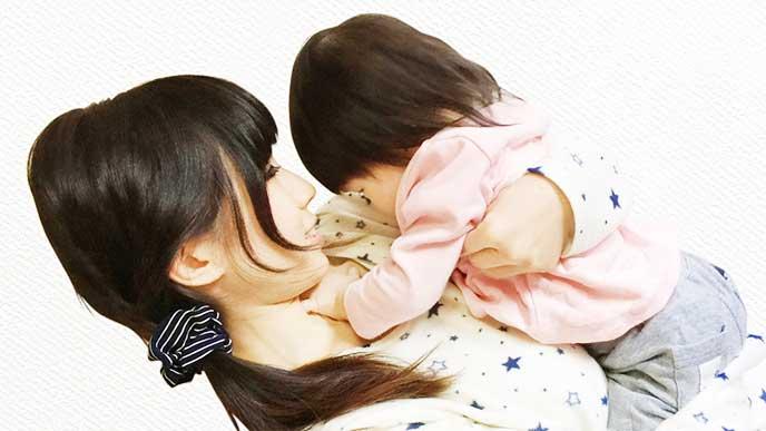 母親に抱っこされて胸に顔を埋めてる女の子
