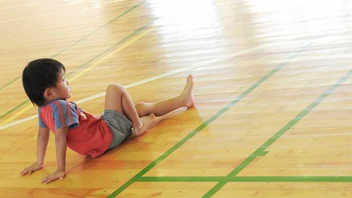 体操教室の床で休んでる男の子