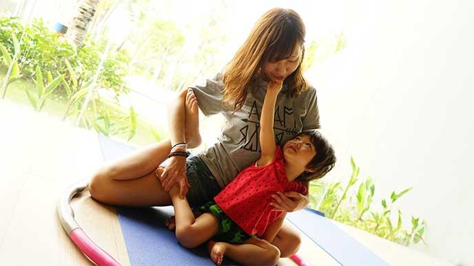 母親と一緒に体操教室でストレッチしてる小さな男のkお