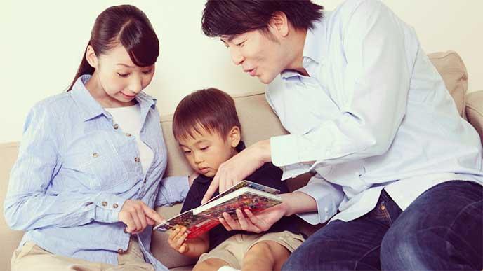 子供と一緒に絵本を見てる夫婦