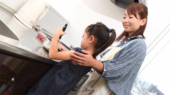 母親と一緒にキッチンで料理をしてる女の子