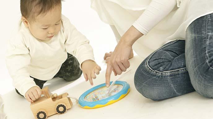 遊ぶ幼児に傍から干渉する親