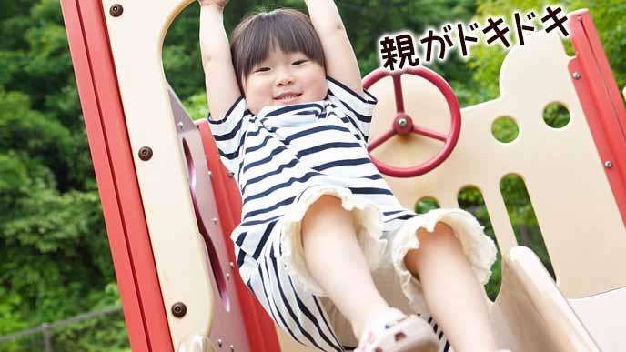 滑り台の枠につかまって笑顔の女の子