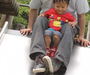 大人と一緒に滑り台にのる子供