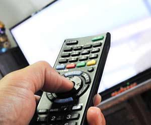 TVのリモコンを押す手