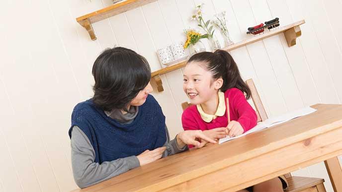 リビングで娘の勉強を見てあげてる母親