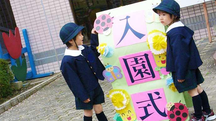 幼稚園の入園式看板の前にいる男の子たち