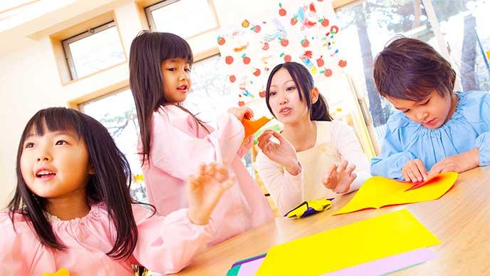 幼稚園で先生と一緒に折り紙をしてる子供達