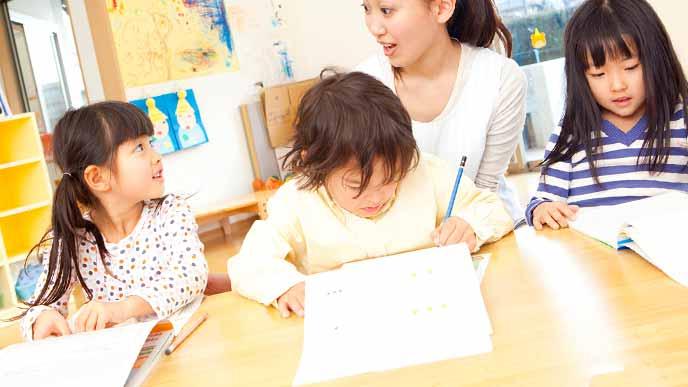 子供に学習ドリルをさせる幼稚園の先生