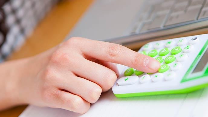 電卓で計算する女性の手