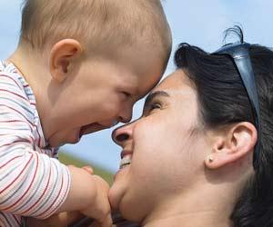 母親の額と自分の額をつけて喜ぶ赤ちゃん