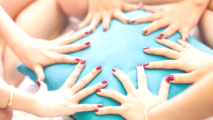 クッションの上で手を並べる女性友達