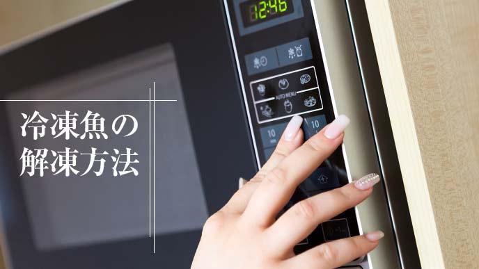電子レンジのボタンを押す主婦