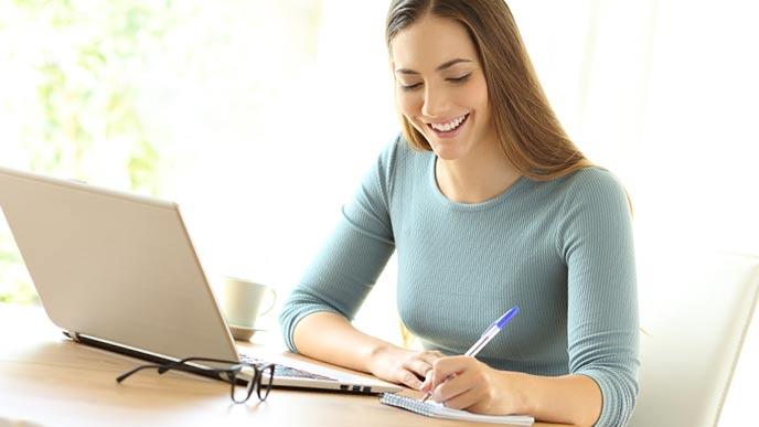 ラップトップを操作しながら勉強する女性