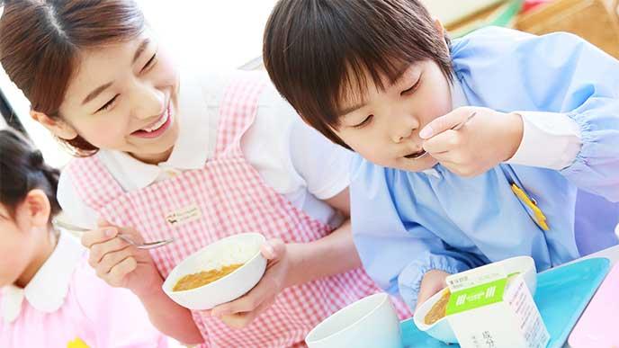 保育園で保育士さんと一緒に給食を食べてる男の子