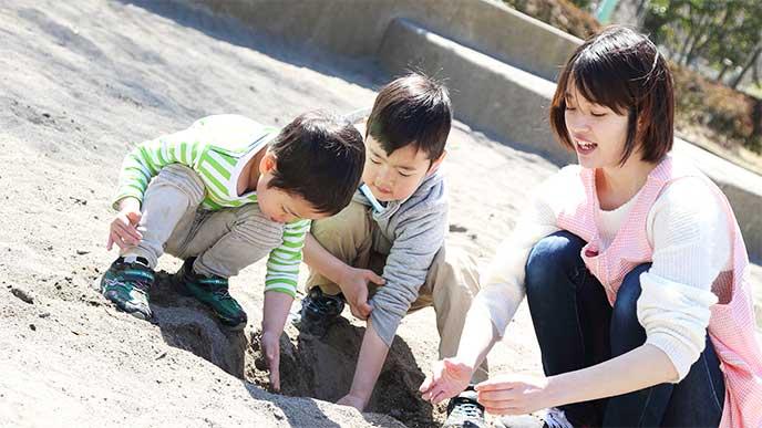 砂場で遊ぶ園児の面倒を見てる保育士さん