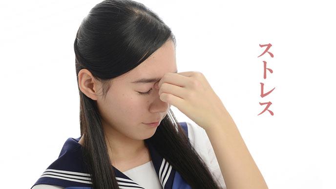 目を閉じて眉間を押さえる女子中学生