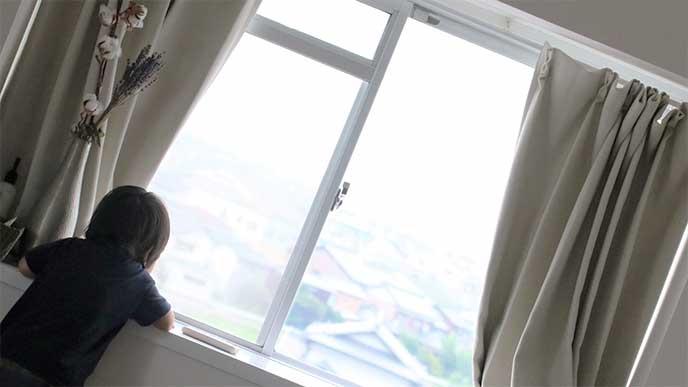 1人で窓から外を見てる男の子