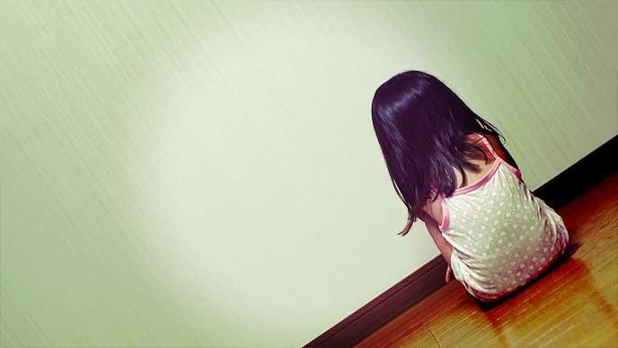 壁に向かって1人で座ってる女の子