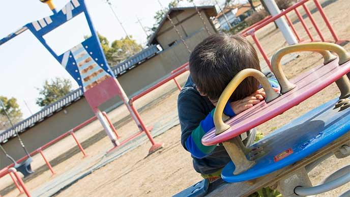 公園の遊具の上で1人で泣いてる男の子