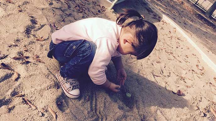 砂場で1人で遊んでる女の子