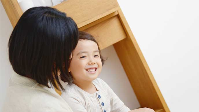 子供を抱っこしながら話しかけてる母親