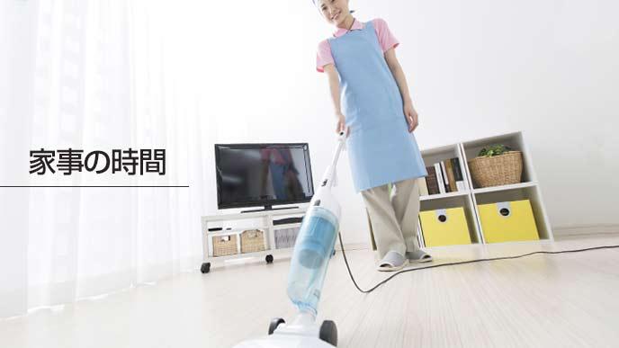 部屋の中で掃除機をかける主婦