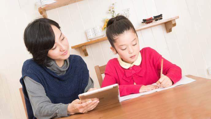 子供の勉強を見守るお母さん