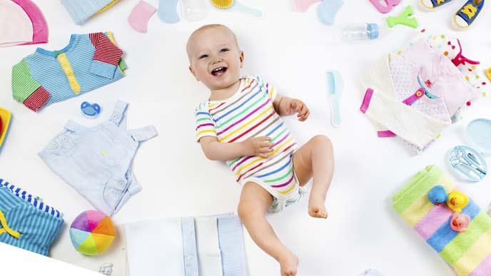 赤ちゃんグッズに囲まれる赤ちゃん