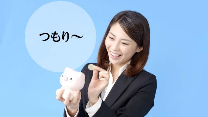 貯金箱に小銭を入れる女性