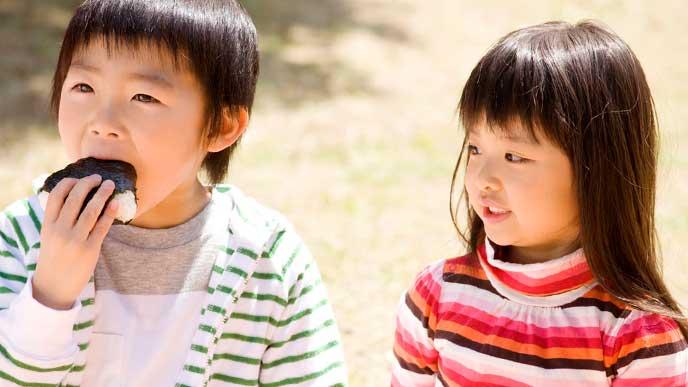遠足でおにぎりを食べている幼稚園児の男の子と隣りで見ている女の子
