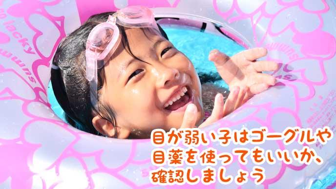 プールで浮き輪から顔を出している幼稚園児の女の子