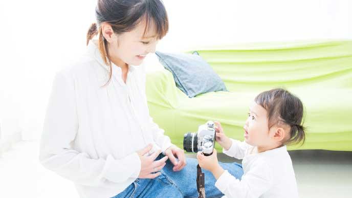 一眼レフカメラを持つ子供と笑顔の母親